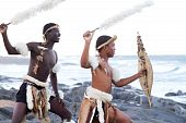 stock photo of zulu  - two young african zulu dancers on beach with shields and traditional clothing - JPG