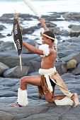 image of zulu  - a tradtional zulu man with shield on the rocks of the beach - JPG