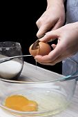 Cracking a brown egg over a glass bowl
