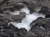 stock photo of oxidation  - Salt precipitation in eroded black oxidized limestone cavities near Mediterranean sea - JPG