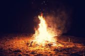 stock photo of bonfire  - The bright big bonfire burns on a beach at night - JPG