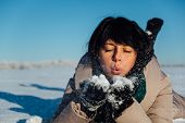 girl lying on the snow and blows snow from hands