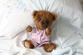 stock photo of pyjama  - Cute teddy bear in pink pyjama resting in the bed - JPG