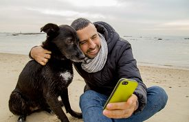 picture of nonverbal  - Man helping his dog making selfie image using a smartphone - JPG