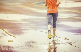 image of rainy weather  - Young woman jogging on asphalt in rainy weather - JPG