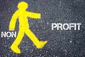 foto of non-profit  - Yellow pedestrian figure on the road walking towards PROFIT from NON PROFIT - JPG