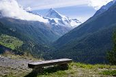 image of snow capped mountains  - Bench with Scenic View of Snow Capped Alps and Overview of Lush Green Mountain Valley on Bright Sunny Day Valais Switzerland - JPG