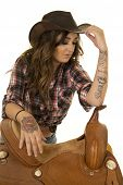 foto of cowgirl  - a cowgirl leaning on her saddle with her hand on her hat - JPG
