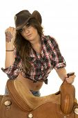 image of cowgirl  - A cowgirl leaning on her saddle with her hand on her hat - JPG