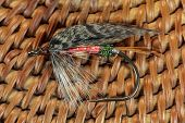 stock photo of trout fishing  - Macro photo of an artificial fly for fly fishing on a basketwork background - JPG