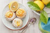pic of pound cake  - Mini lemon bundt cakes dusted with icing sugar and fresh lemons over rustic wooden background - JPG