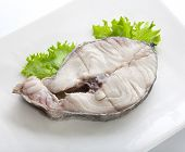 image of cod  - Fried stake of cod with fresh green lettuce on the white plate - JPG