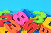 pic of blue things  - Heap of plastic colored numbers on a blue background close up - JPG
