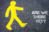 picture of pedestrians  - Yellow pedestrian figure on the road walking towards Are We There Yet Conceptual image with Text message over asphalt background - JPG