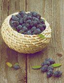 stock photo of honeysuckle  - Fresh Ripe Honeysuckle Berries with Leafs in Wicker Bowl on Rustic Wooden background - JPG