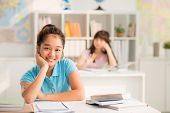 picture of schoolgirls  - Cheerful lovely schoolgirl sitting at her desk and looking at the camera - JPG