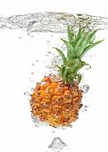 Small Pineapple Falling In Water On White