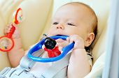foto of teething baby  - baby laying in bouncer chair with toys - JPG
