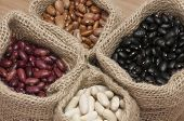 stock photo of kidney beans  - White beans, kidney beans, pinto beans and black beans, in small bags.