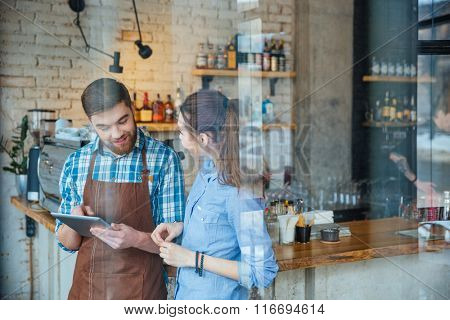 Cheerful bearded young waiter in brown apron talking to young woman and showing information on table