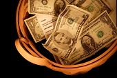 stock photo of tithe  - a basket of money representing charity and offering and giving - JPG