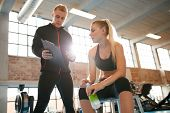 Постер, плакат: Personal Trainer Making An Exercise Plan For Young Woman