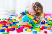 Little Girl Playing With Colorful Toy Blocks poster