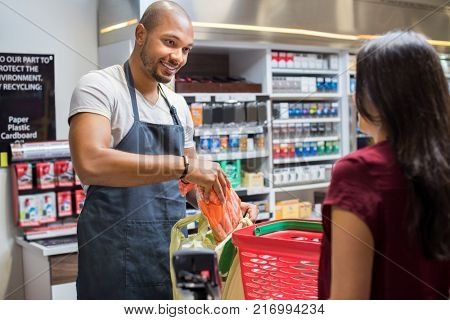 poster of Smiling salesman putting vegetables in bag for customer after billing. Cashier black man at grocery