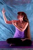 Woman In Half Lotus Yoga With Hands In Dancing Shiva Position