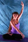 Woman In Half Lotus Yoga Prayer Position With Arm Up Hand In Om Mudra