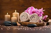 Spa setting with brown rolled towel, orchids and candles on wood. Relaxing spa concept with candles, poster