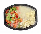 picture of frozen tv dinner  - A still frozen TV dinner with pasta and vegetables in black dish - JPG