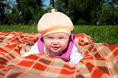 Portrait of the baby, on coverlet in the park