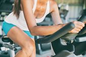 Indoor cycling woman doing HIIT cardio workout biking on indoors gym bike. Girl cyclist working out  poster