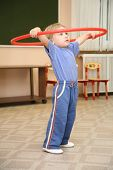 pic of hula hoop  - Little girl doing different exercises with hoop - JPG