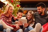 Christmas entertainment at home smiling family watching video on digital tablet poster