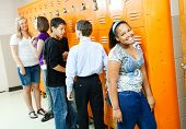 Teenagers in the hallway, at their lockers between classes.