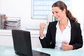 Smart woman punching the air in delight after looking at her laptop