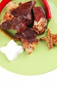 roast meat chunks on green  plate over white