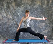 Woman Doing Yoga Posture Rotated High Lunge