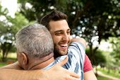 Adult son hugging his senior dad poster