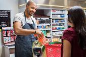 Smiling salesman putting vegetables in bag for customer after billing. Cashier black man at grocery  poster
