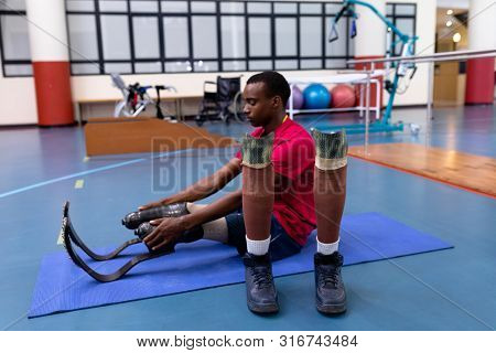poster of Side view of African-american disabled man exercising on exercise mat in sports center. Sports Rehab