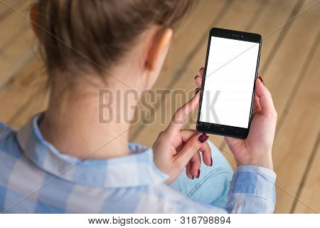 poster of Mockup Image: Woman Looking At Black Smartphone With White Blank Screen. Close Up View Of Woman Hand