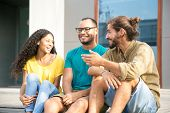 Happy Multiethnic Friends Chatting Outside. Cheerful Mix Raced Young Men And Woman Sitting Outdoors, poster