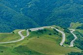 Winding Road In A Mountain Valley. Winding Asphalt Road In A Mountain Green Valley. poster