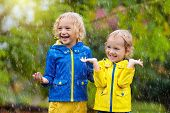Kids Play In Autumn Rain. Child Playing Outdoor On Rainy Day. Little Boy Catching Rain Drops Under H poster