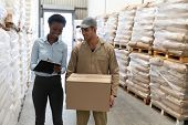 Front view of male worker and female manager discussing on clipboard in warehouse. This is a freight poster