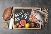 Chalkboard With Phrase Food Allergy And Different Products On Dark Grey Background, Flat Lay poster