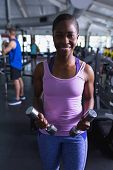 Close-up of African-american fit woman exercising with dumbbells in fitness center. Bright modern gy poster